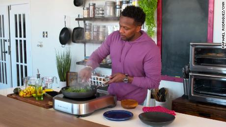 Curry prepares salmon with spinach, cauliflower rice and mango salsa in his Dallas test kitchen.