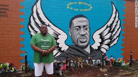 Travis Cains stands alongside a George Floyd mural.